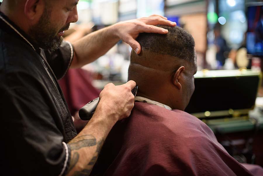 V's barber giving a patron a neck trim