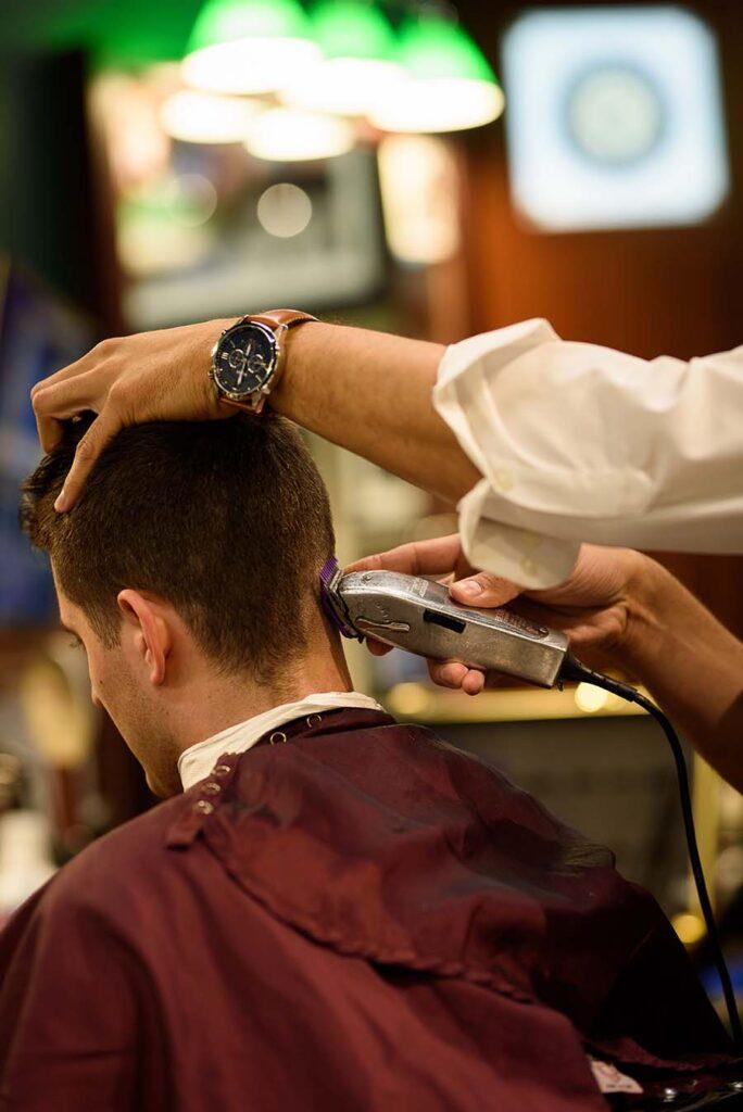 V's barber giving a patron a skin fade